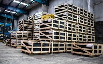 The inside of a warehouse with pallets racked high, all holding black-wrapped goods.