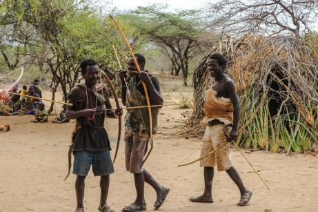 Hadzabemänner bei ihren Bogenschießübungen