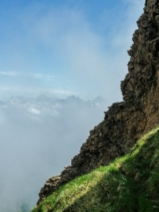 Langsam erheben sich die ersten Bergspitzen aus den Wolken