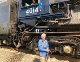 In this colour photograph the designer Ian Logan is dwarfed by the Union Pacific locomotive Big Boy 4014.