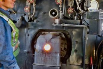 In this colour photograph a crew member has opened the spy hole into the firebox to assess the state of the fire.