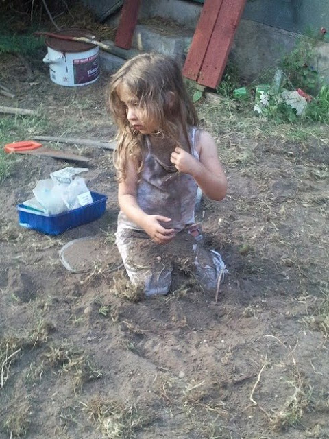 Ella putting soil all over her