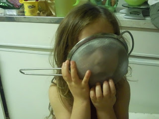 Ella with her face in a sieve