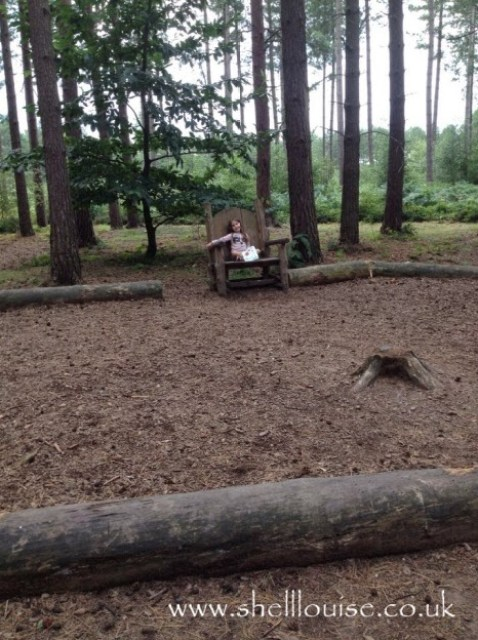 Ella sitting on a wooden chair in the woods