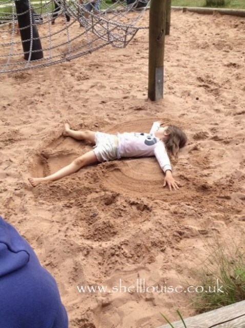 Ella making a sand angel