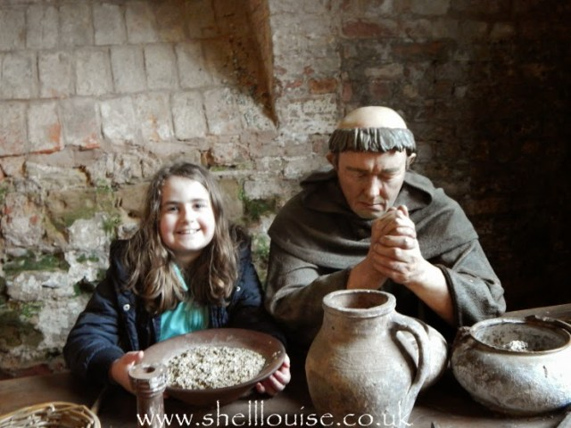 Kaycee sitting next to a statue of a monk at Rufford Abbey