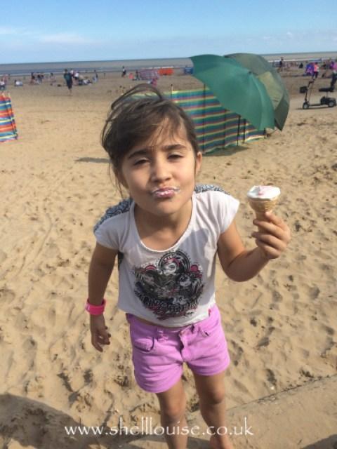 Ella eating ice cream on the beach