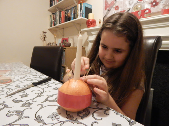 KayCee putting the sweets on her Christingle