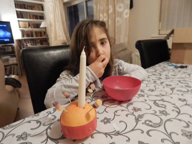 Ella eating the sweets that are for the Christingle!