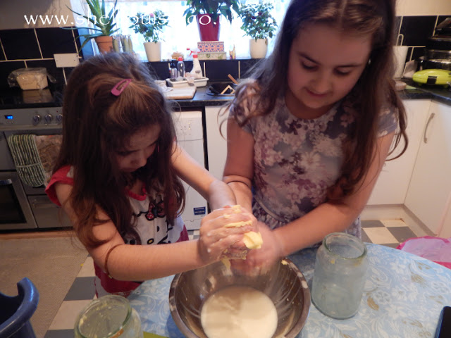 The girls squeezing the butter milk out of the butter