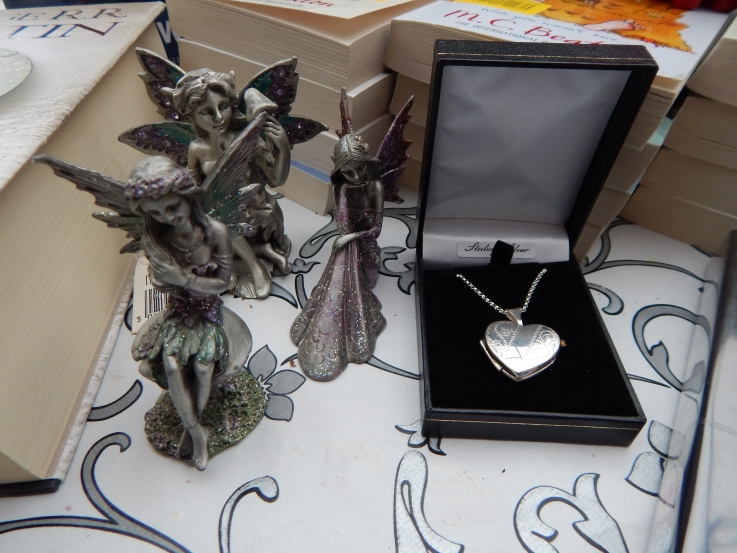 Unwrapped birthday presents, silver locket, pewter fairies