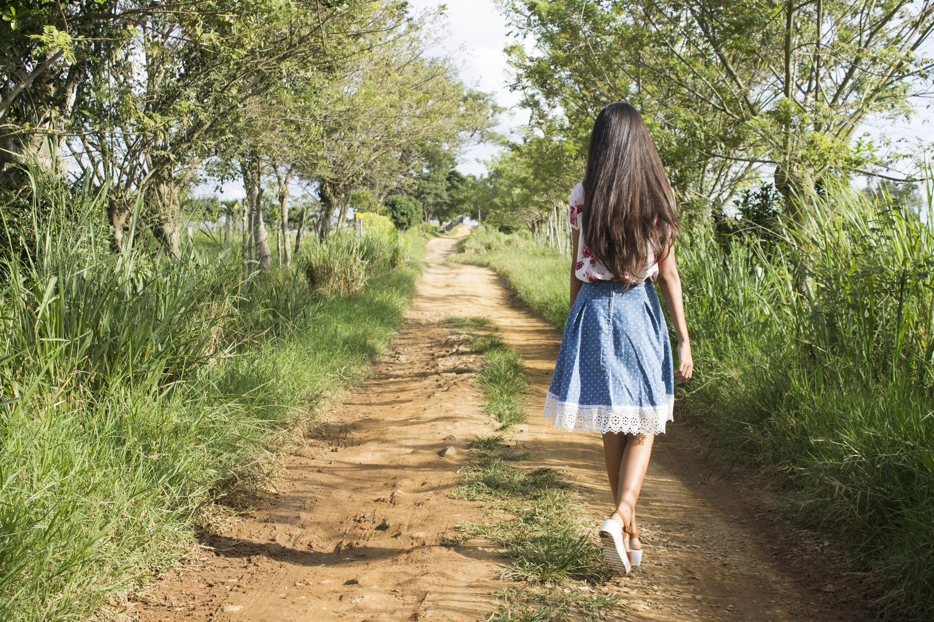 teenage daughter walking down a dirt track