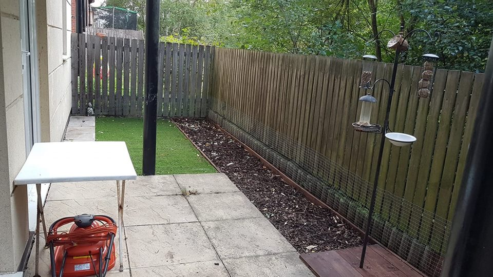 Granddad's garden with new artificial grass and a border laid with bark