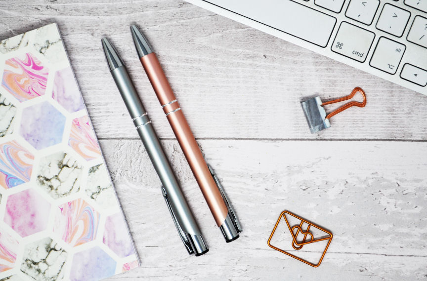blog flatlay - white keyboard, silver pen, rose gold pen, envelope shaped paperclip, bulldog clip