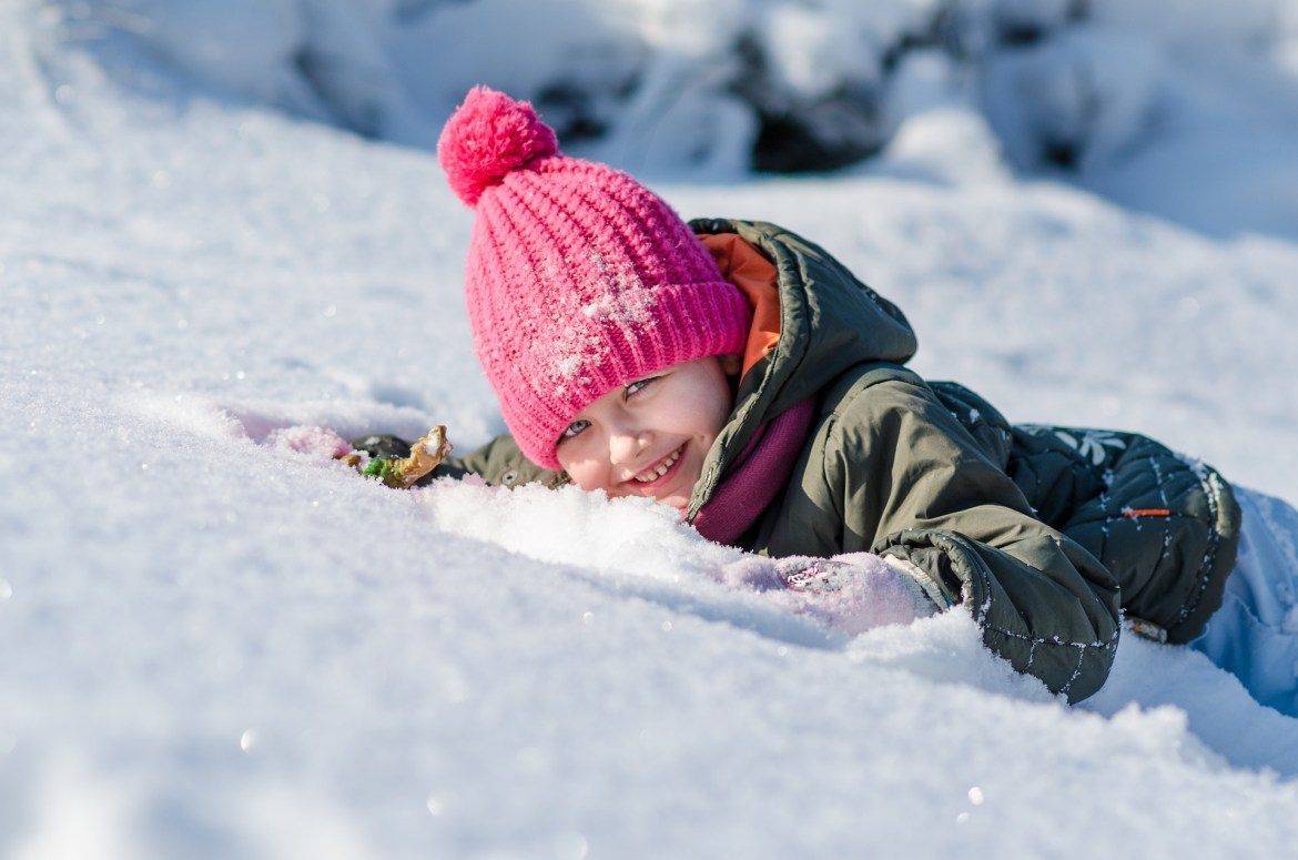 child lying in the snow