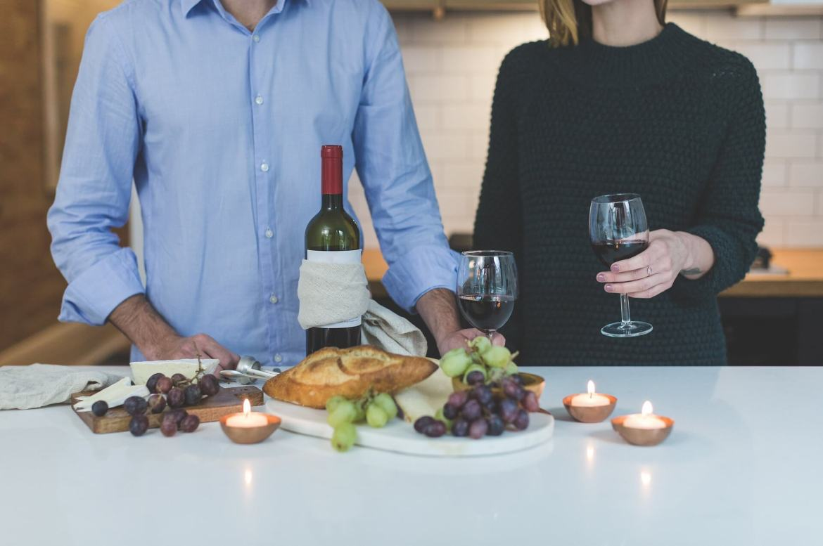 a couple sharing a bottle of wine. There's food and candles on the counter in front of them