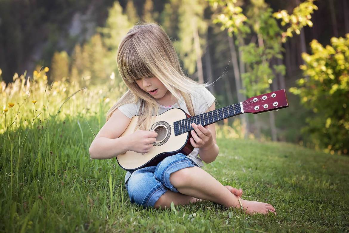 child playing a guitar - encourage hard work and practice by praising effort