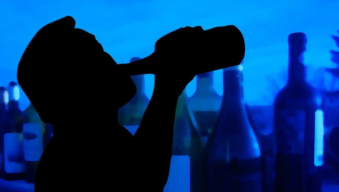 silhouette of a man drinking a bottle of alcohol - addiction. rehabilitation