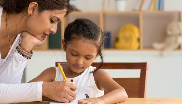 woman helping girl with homework