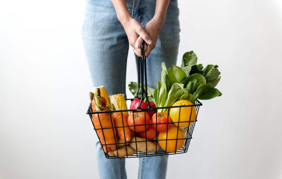 Woman carrying shopping basket full of fruit and vegetables - healthier