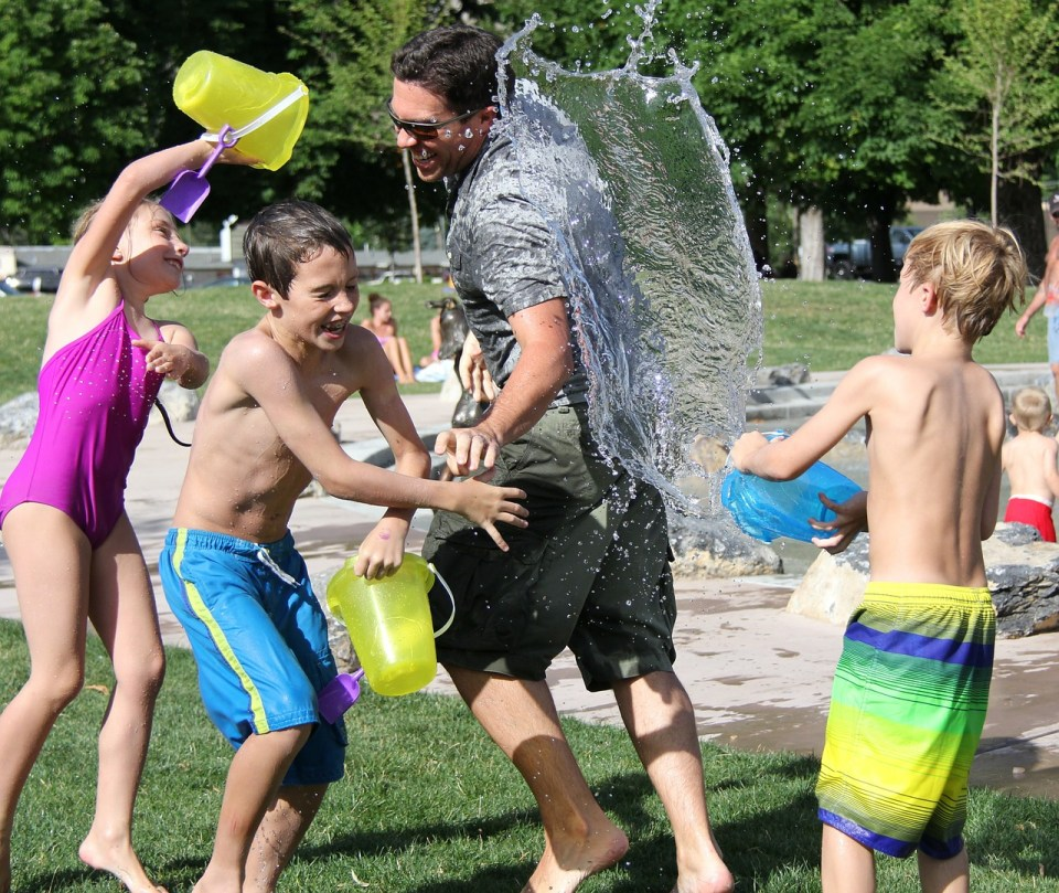 Parents and children having a water fight - becoming a fit parent
