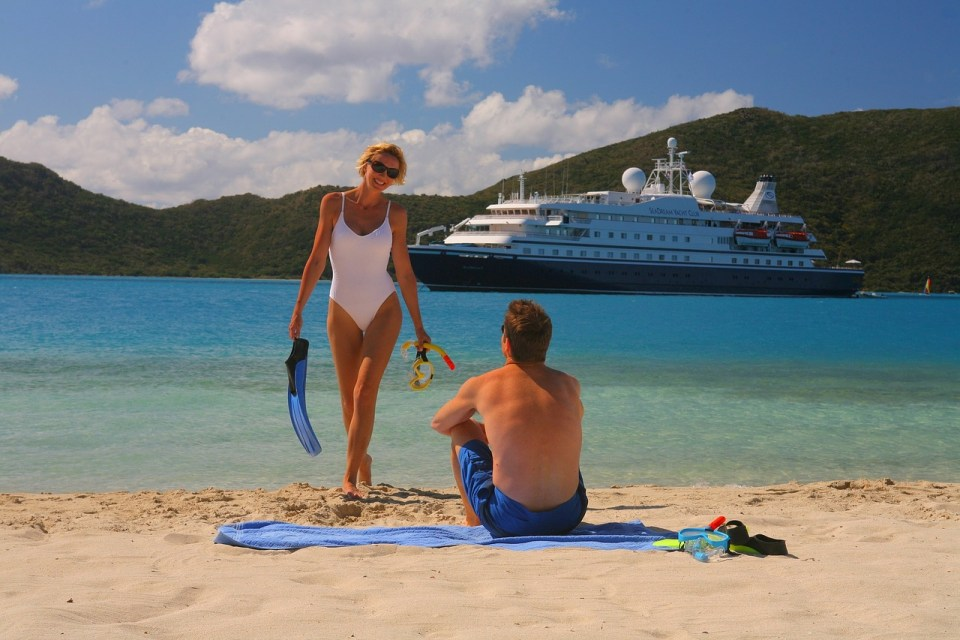 man and woman on the beach with a crusie ship in the background