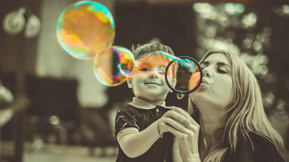 mum and son blowing bubbles - role of family in education
