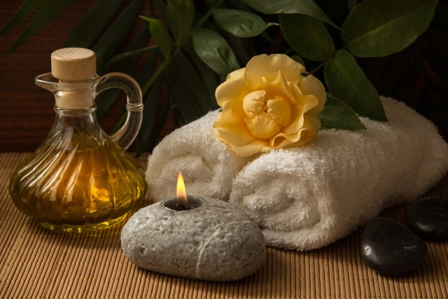massage oil, a candle and white towels