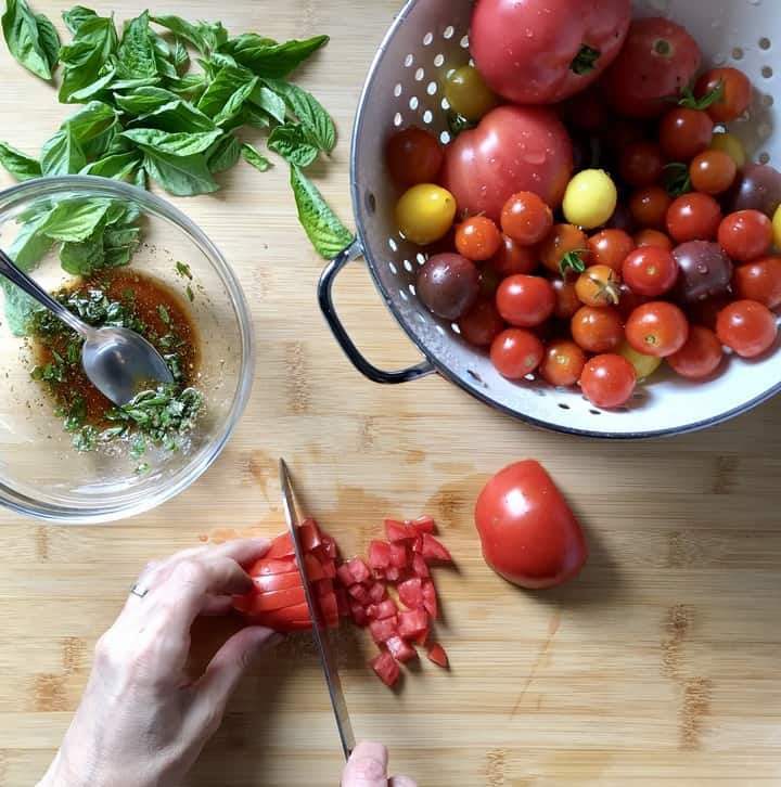 Tomatoes are being diced on a wooden board.