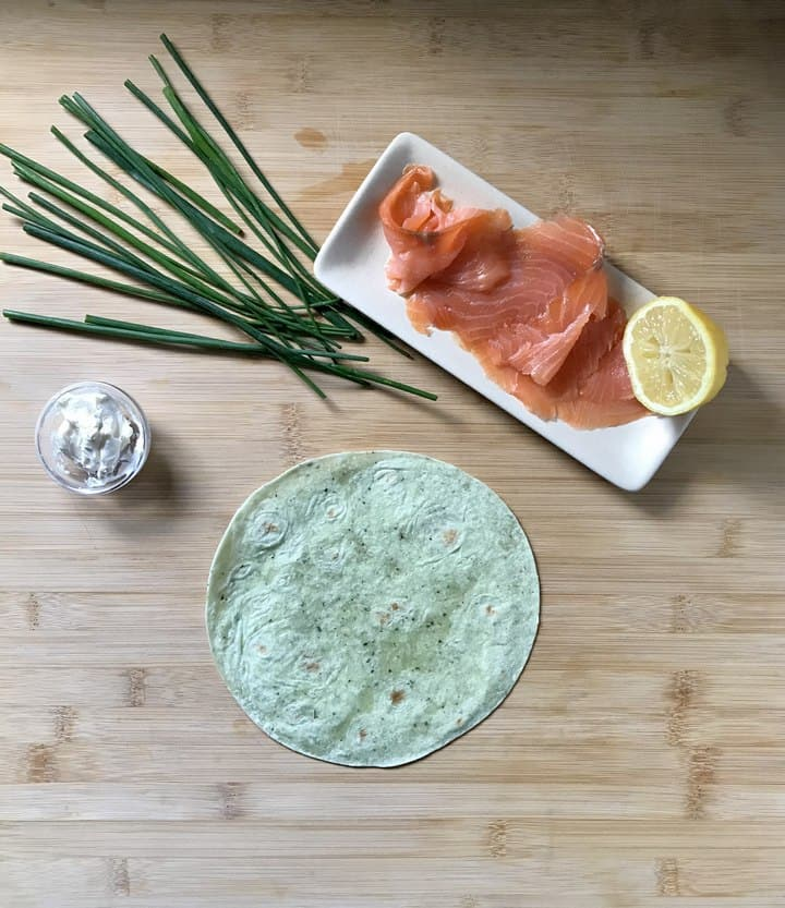 The ingredients to make salmon pinwheels are on a wooden board.