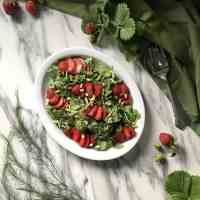 A refreshing salad made with arugula, strawberries and pine nuts.