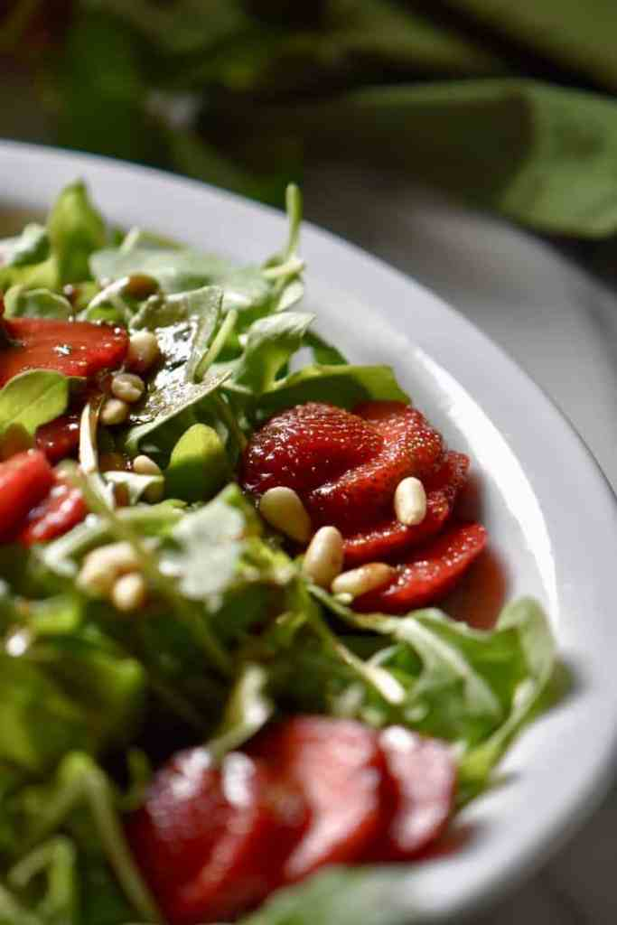 A summer salad with arugula and strawberries in a white oval dish.