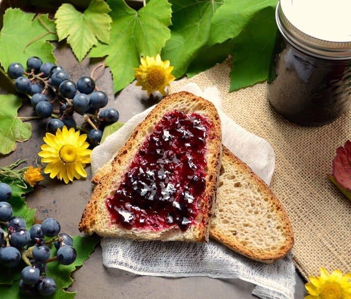An overhead shot of the purple concord grape jelly spread over a slice of whole wheat bread.