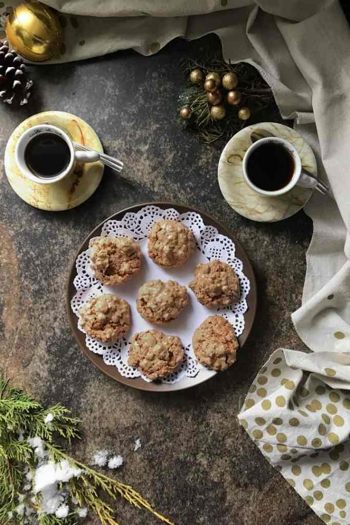 An overhead shot of the brutti and buoni cookies on a small plate, surrounded by 2 espressos and Christmas decorations.