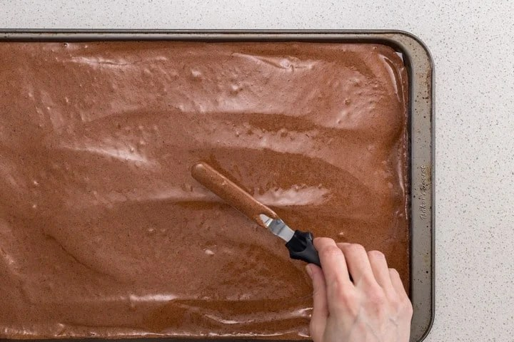 The chocolate batter is being spread evenly on the sheet pan.
