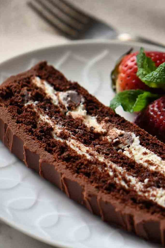 A slice of Chocolate Cream Cake on a white serving plate.