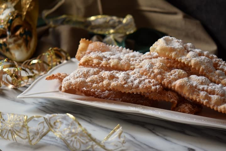 Stacks of crispy crostoli on a white ceramic dish, ready to be served.