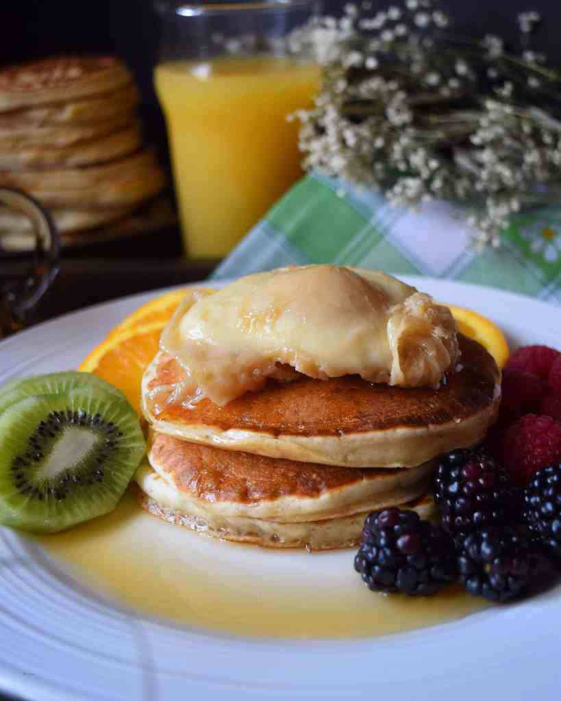 A maple poached egg placed over pancakes, surrounded by fresh fruit.