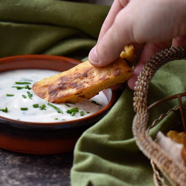 Chickpea flour stick being dipped in a yogurt sauce.