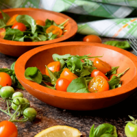 A bowl of cherry tomato and arugula salad.