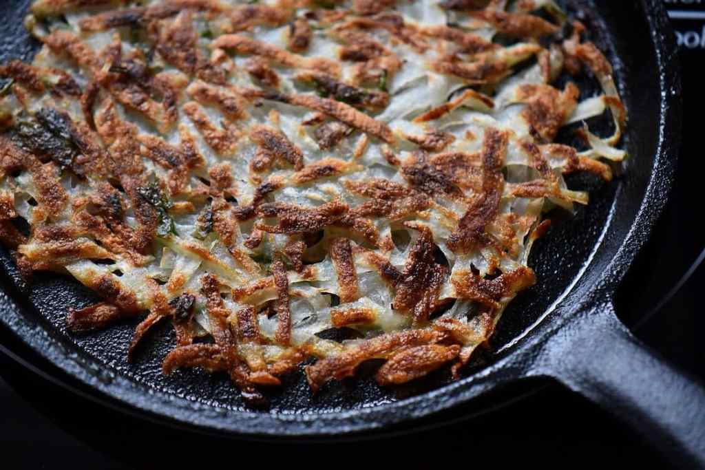 A close up of a crispy hash brown in a cast iron pan.
