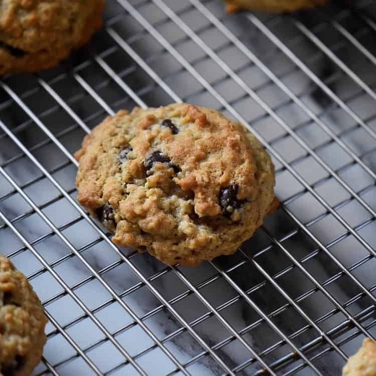 Thick and Chewy Oatmeal Chocolate Chip Cookies on a cooling rack.