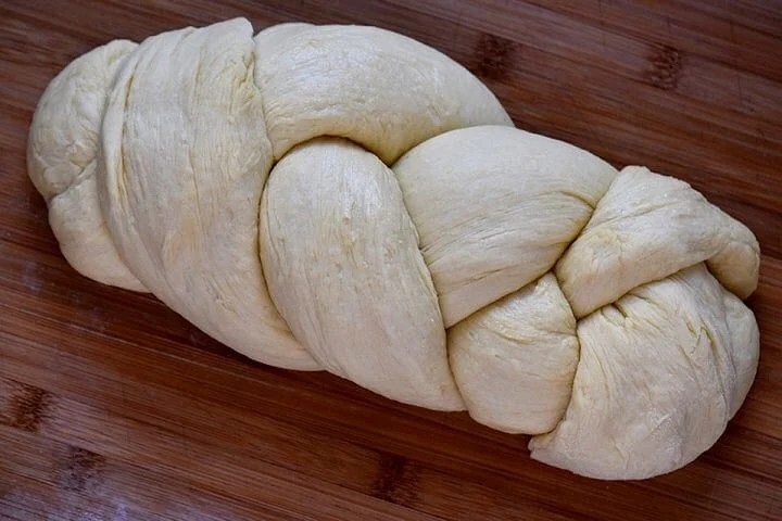 An unbaked braided version of Italian Easter Bread on a wooden board.