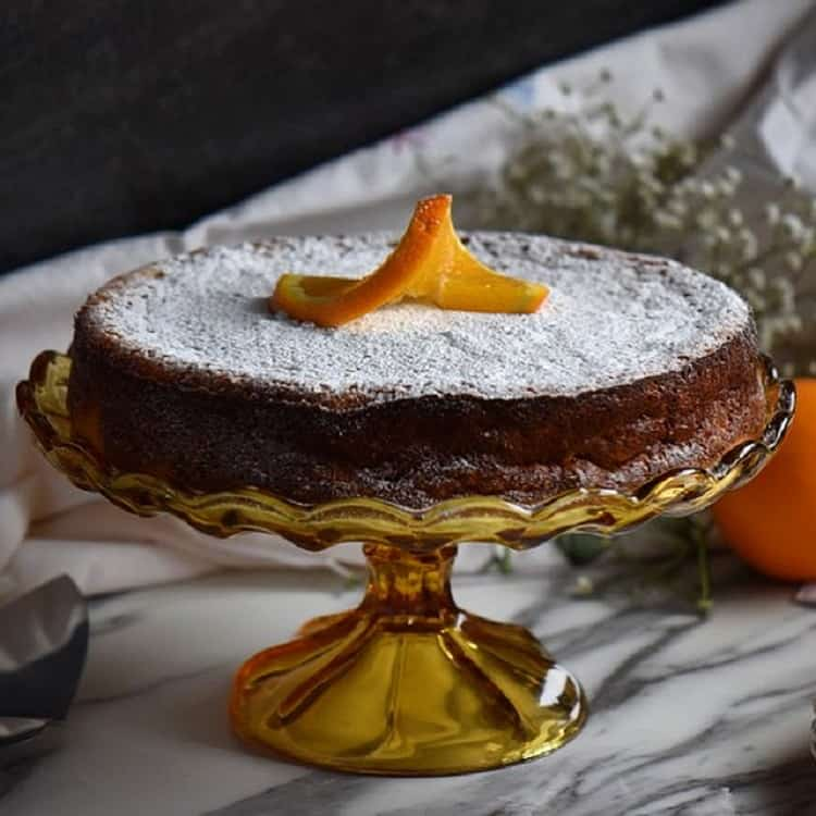 The rice ricotta Easter pie set on a cake platter with a dusting of icing sugar and a slice of orange placed decoratively over the top.