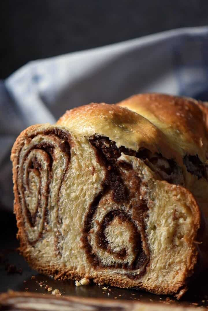 The chocolate nutty swirls of a sliced Romanian yeast bread called cozonac.