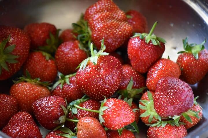 Bright red freshly picked strawberries are in a colander, ready to be rinsed.