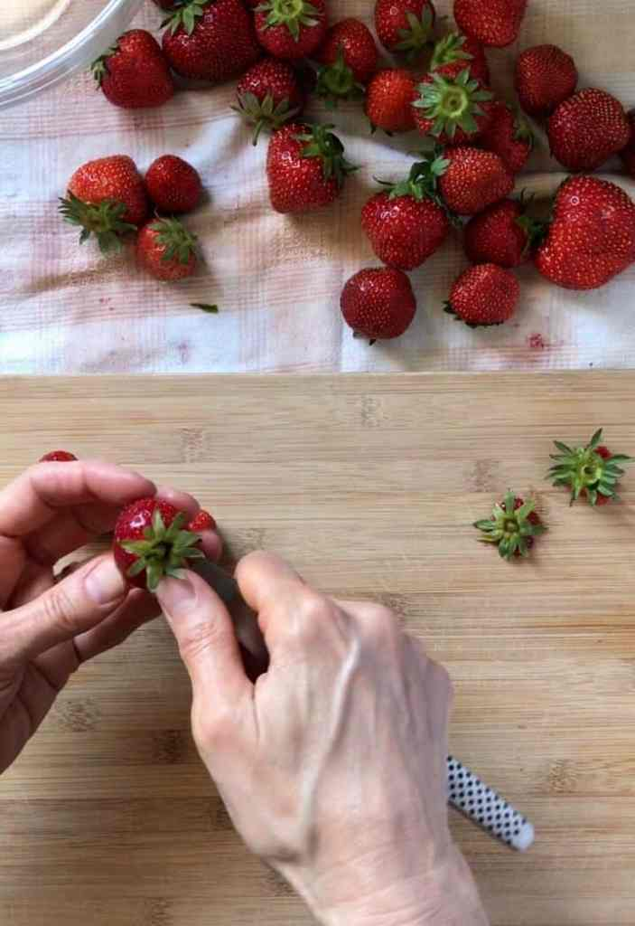 One of the steps on how to freeze strawberries involves the removal of the hull. In this picture, a paring knife is used.