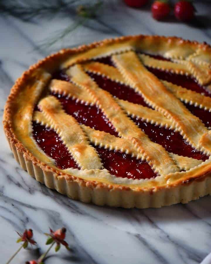 The strawberry jam is peaking through the lattice top of the crostata.
