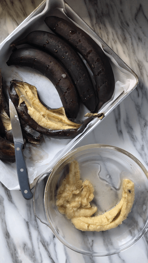 An overhead shot of Roasted Bananas in the process of being sliced open with a knife and transferred to a bowl.