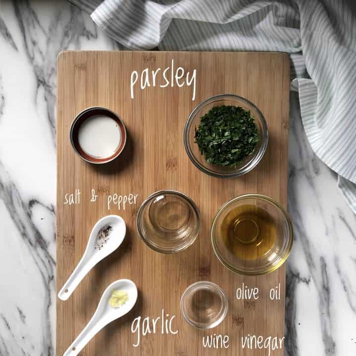 The ingredients used to make the parsley vinaigrette are measures and placed on a wooden board, ready to be mixed together.